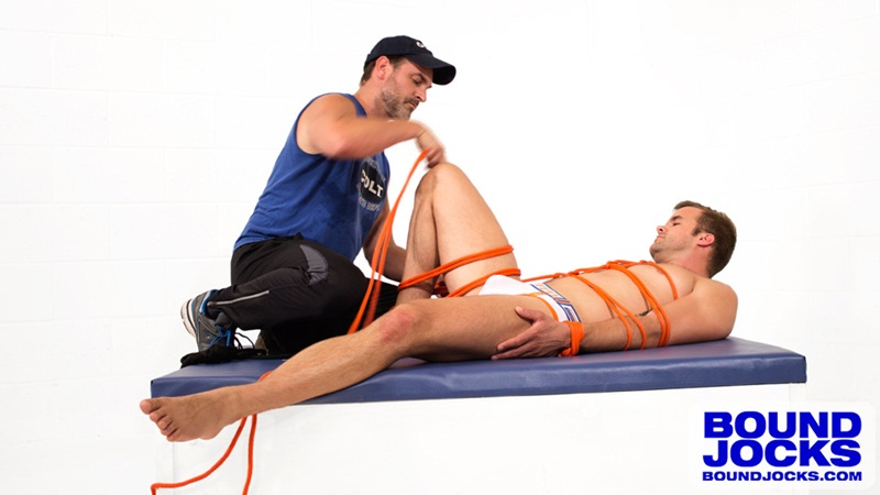 Mr. Kristofer massages bound jock Connor Patricks' cock through his jock strap